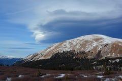 在积雪的山上面的奇怪的双突透镜的云彩 免版税库存照片
