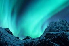在积雪的山峰上的极光borealis 免版税库存照片