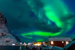 在积雪的议院上的北极光 免版税库存照片