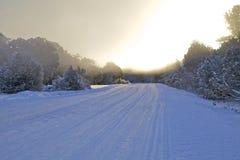 在积雪的路的日出 免版税库存照片