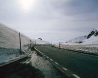 在积雪的风景的一条空的柏油路在阿尔卑斯瑞士 免版税库存图片