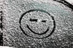 在积雪的玻璃画的一张兴高采烈的面孔 库存图片
