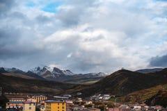 在积雪覆盖的山下的村庄 库存照片
