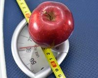 在称量器的苹果计算机有英寸磁带的,吃健康和维护的好身体容积指数的概念 图库摄影
