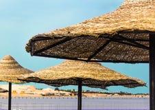 在秸杆三遮光罩蓝天海水沙滩外面的沙滩伞在晴朗的夏日 免版税图库摄影