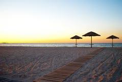 在秸杆外面的一些把沙滩伞在沙子在海早晨夏天阳光周末附近落后 库存图片