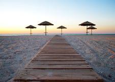在秸杆外面的一些把沙滩伞在沙子在海早晨夏天阳光周末附近落后 免版税库存图片