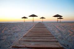 在秸杆外面的一些把沙滩伞在沙子在海早晨夏天阳光周末附近落后 免版税图库摄影