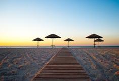 在秸杆外面的一些把沙滩伞在沙子在海早晨夏天阳光周末附近落后 库存照片