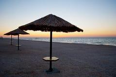 在秸杆外面的一些把沙滩伞在沙子海岸早晨晒黑日出周末 免版税库存照片