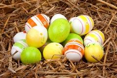 在秸杆嵌套隐藏的五颜六色的被绘的复活节彩蛋  免版税库存图片