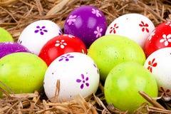 在秸杆嵌套隐藏的五颜六色的被绘的复活节彩蛋  库存照片