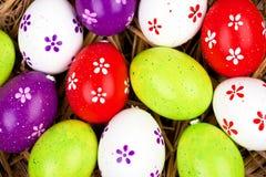 在秸杆嵌套隐藏的五颜六色的被绘的复活节彩蛋  图库摄影