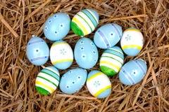 在秸杆嵌套隐藏的五颜六色的被绘的复活节彩蛋  免版税库存照片