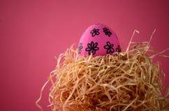 在秸杆巢的装饰的手画明亮的桃红色花卉复活节彩蛋反对与拷贝空间的深红背景 库存图片