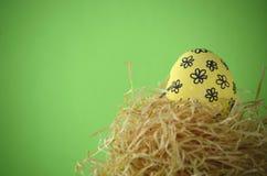 在秸杆巢的装饰的手画黄色花卉复活节彩蛋反对与拷贝空间的明亮的黄色背景 库存照片