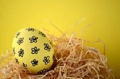 在秸杆巢的装饰的手画黄色花卉复活节彩蛋反对与拷贝空间的明亮的黄色背景 免版税库存照片
