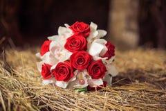 在秸杆的红色新娘的花束 库存照片