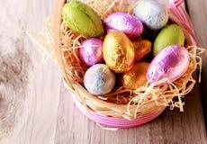 在秸杆篮子的五颜六色的复活节彩蛋 免版税库存图片