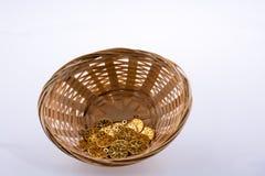 在秸杆篮子的假金币 免版税库存照片