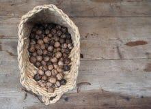 在秸杆篮子的新近地被采摘的核桃在老被风化的木背景 库存照片