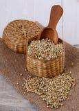 在秸杆篮子的未加工的荞麦在木背景 免版税库存图片