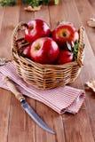 在秸杆篮子的红色有机苹果在木背景 库存图片