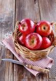 在秸杆篮子的红色有机苹果在木背景 免版税库存图片