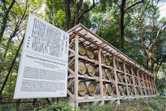 在秸杆酒包裹的日本桶堆积在与描述的架子上 免版税库存图片