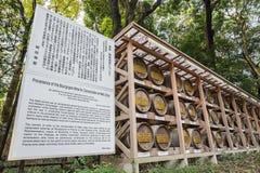 在秸杆酒包裹的日本桶堆积在与描述的架子上 库存照片
