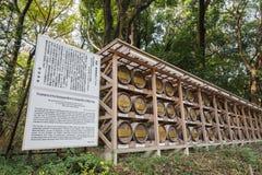 在秸杆酒包裹的日本桶堆积在与描述的架子上 免版税库存照片