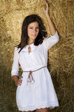 在秸杆附近的美丽的新农厂妇女打包墙壁 库存图片