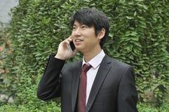 在移动电话的亚洲新生意人 库存照片