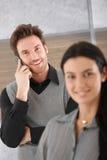 在移动电话的微笑的生意人 库存照片