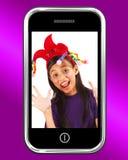 在移动电话的愉快的女孩照片 免版税库存图片