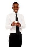在移动电话的非洲男性经理读取消息 库存照片