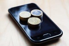 在移动电话顶部的欧洲硬币 库存照片
