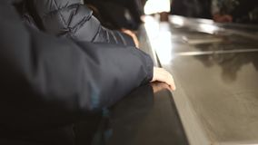 在移动的自动扶梯的特写镜头手在地铁 股票录像