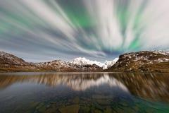在稀薄的云彩后的北极光在山脉 免版税图库摄影
