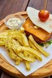 在稀薄的自创皮塔饼面包的一个巨大的水多的汉堡与绿色莴苣、熔化切达干酪、小牛肉炸肉排和樱桃汤姆板料  免版税图库摄影