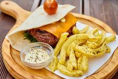 在稀薄的自创皮塔饼面包的一个巨大的水多的汉堡与绿色莴苣、熔化切达干酪、小牛肉炸肉排和樱桃汤姆板料  库存图片