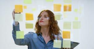 在稠粘的笔记的女实业家文字黏附了在玻璃4k 股票录像