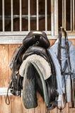 在稳定的门前面的马鞍 免版税库存照片