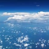 在空中的飞机飞行在云彩上 清楚的天空背景 免版税库存图片