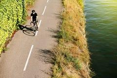 在空中近的河法国上的成人人骑马自行车 图库摄影