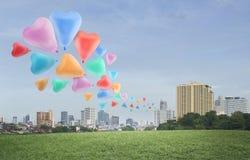 在空气的五颜六色的心脏爱气球浮游物在城市背景 库存图片