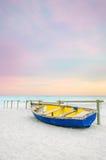 在空白海滩的老黄色蓝色木小船在日落 库存图片