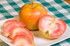 在空白牌照切的桃红色珍珠苹果 免版税库存图片
