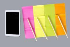 在空白的五颜六色的笔记旁边的手机 库存图片