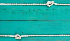 在空白的古色古香的小野鸭蓝色土气木背景的白色绳索边界 免版税图库摄影
